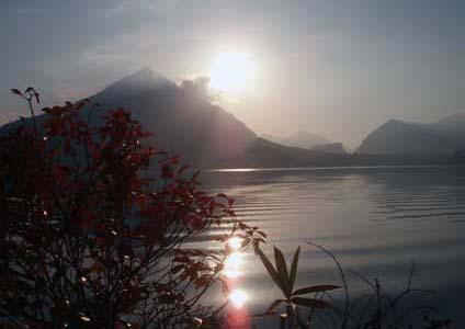 Ein See vor einem Berg, der die Sonne verdeckt